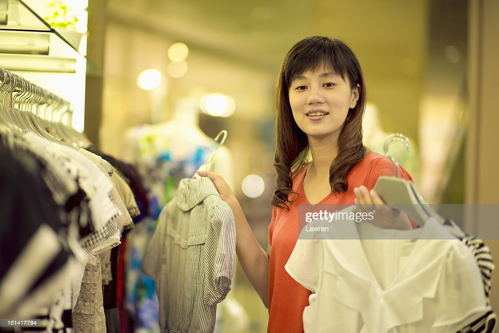 Woman chooses dresses in store : Stock Photo