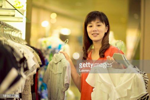Woman chooses dresses in store : Foto de stock