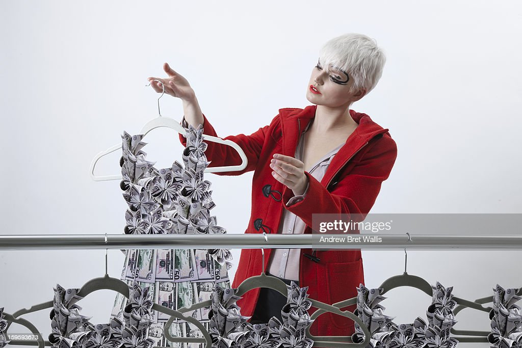 Woman chooses origami dollar dress from a rail : Stock Photo