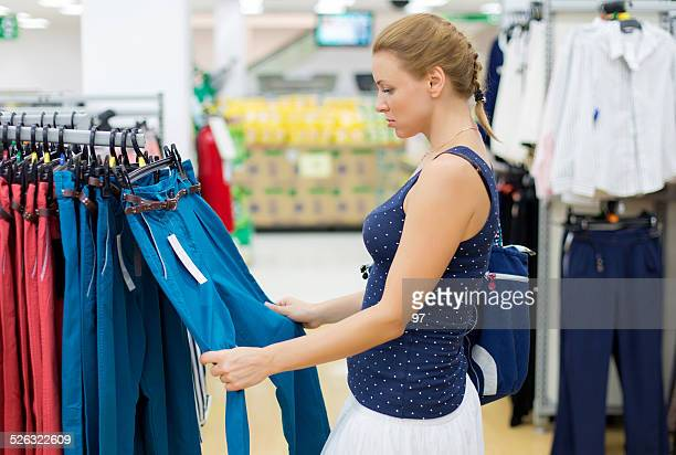 woman chooses pants in the store