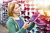 Woman chooses running shoes in the store