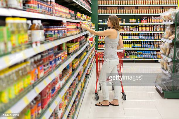 woman chooses sauce in the supermarket