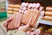 Woman chooses sausages in a vacuum package at the grocery store