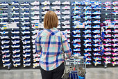 Woman chooses sneakers in a sports clothing store