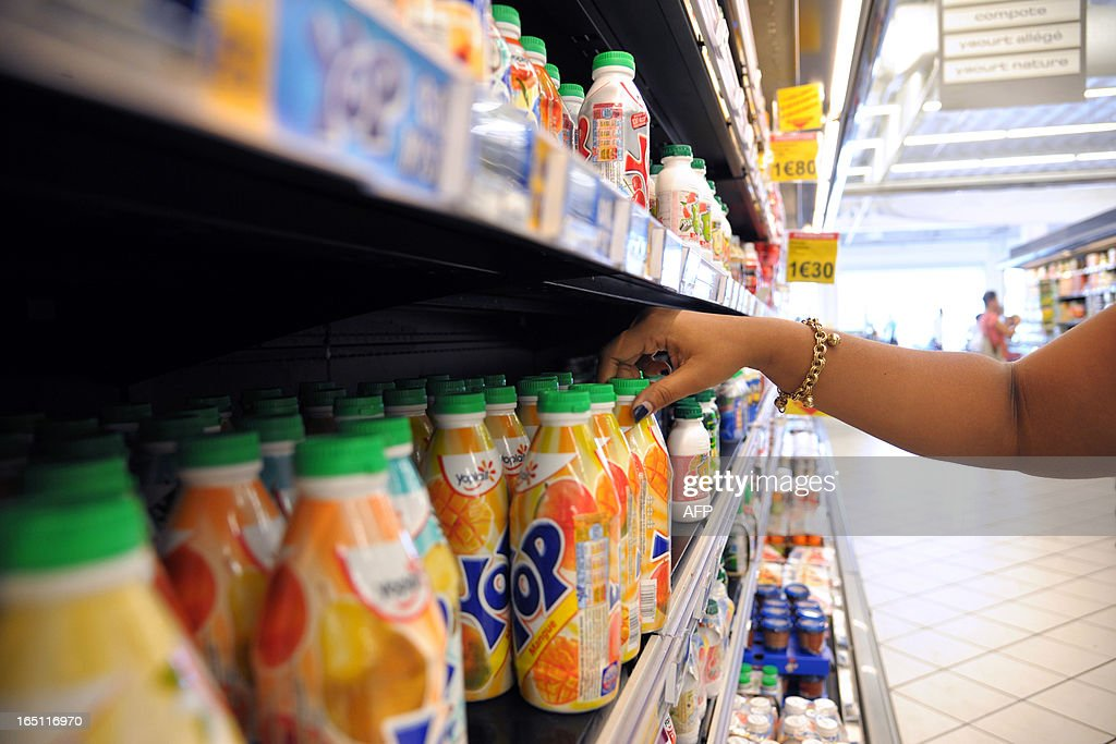 A woman chooses some dairy products in a supermarket of Fort-de-France, on March 30, 2013 in the French caribean island of La Martinique. The French national assembly on March 27, 2013 ruled to align the additional sugar rates of the products sale in the overseas territories with the mainland's rates. AFP PHOTO JEAN-MICHEL ANDRE
