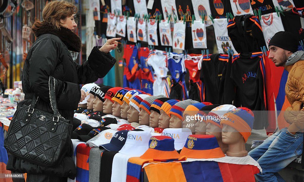 A woman chooses souvenirs with national flag colours in the Armenian capital Yerevan, on February 17, 2013. Armenia's presidential election is set for February 18. AFP PHOTO / KAREN MINASYAN