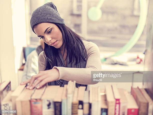 Woman choosing a book in library.