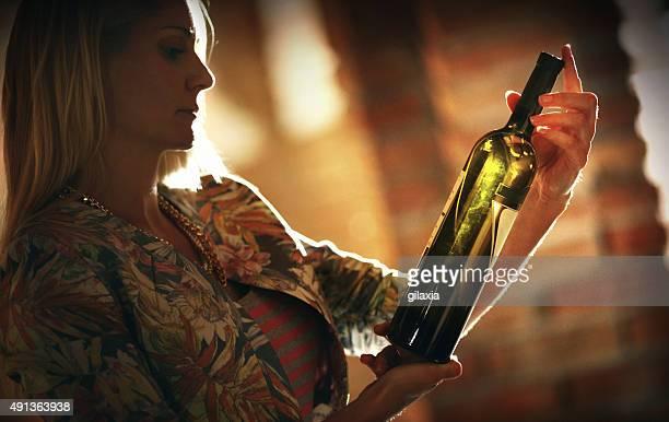 Donna scegliendo un vino in una cantina di vini.
