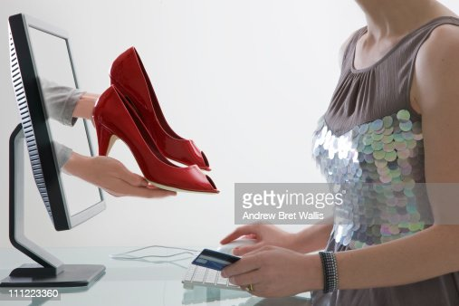 woman choosing and paying for shoes via computer : Foto de stock
