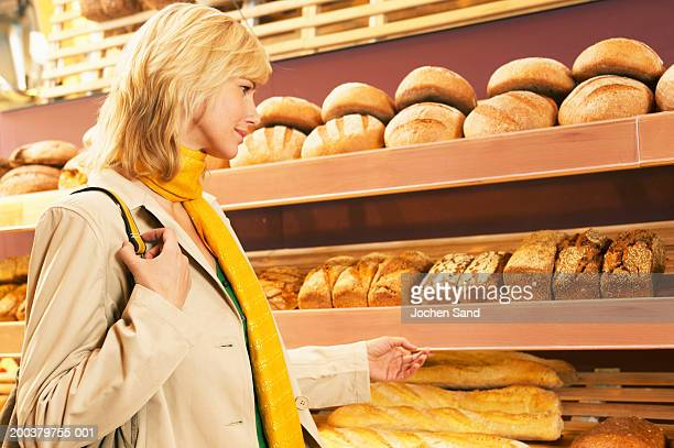Woman choosing bread in supermarket, smiling