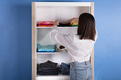 Rear View Of A Young Woman Choosing Cloth From Shelf