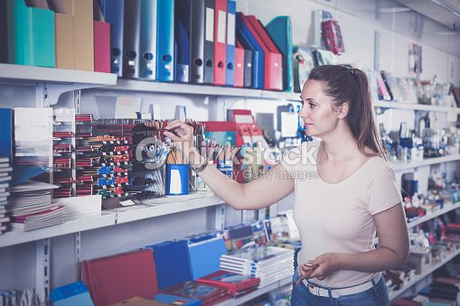 woman choosing color pencil, different color copybook in stationery shop : Stock Photo
