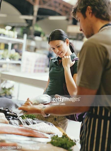Woman choosing fish in market, smiling (focus on woman)