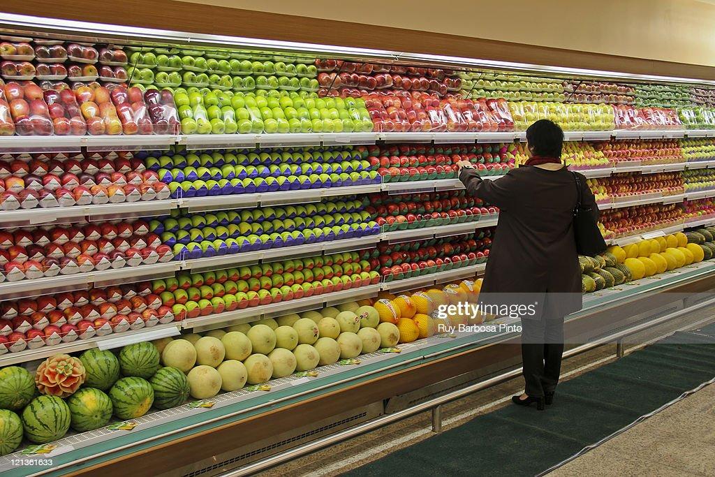 Woman choosing fresh fruits : Stock Photo