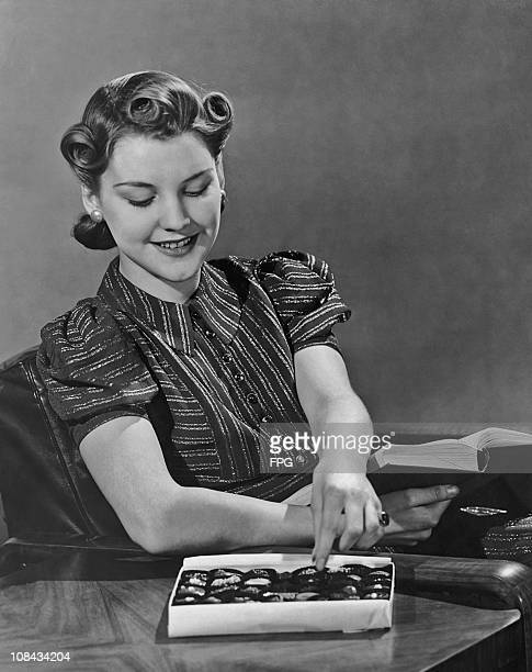 A woman choosing from a box of chocolates circa 1940