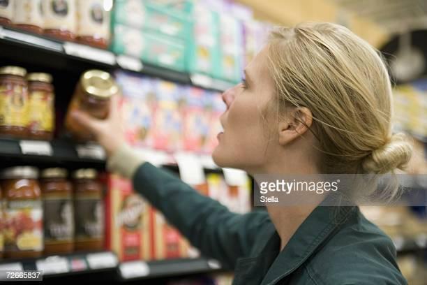Woman choosing jar from supermarket shelf