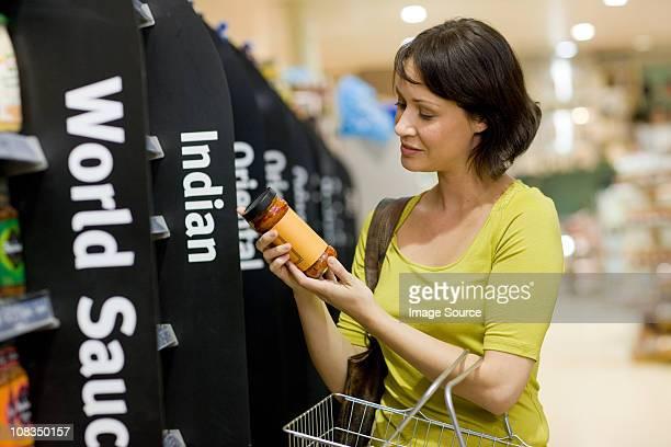Woman choosing jar of sauce in supermarket