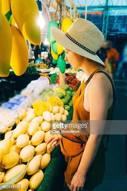 Woman choosing mango in market