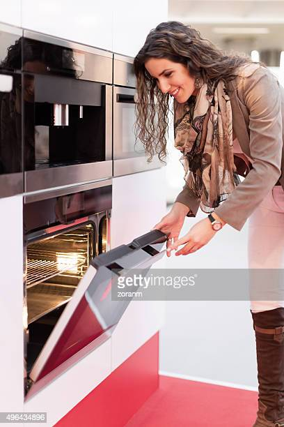 Woman choosing oven in store