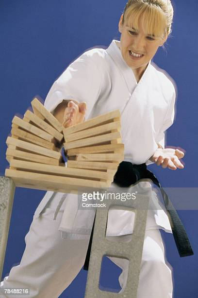 Woman chopping boards with martial arts technique