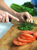 Woman chopping herbs, close-up