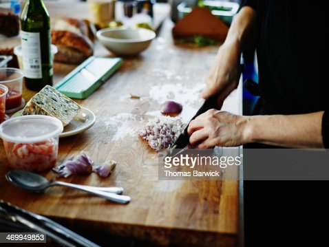 Woman chopping onion on kitchen counter