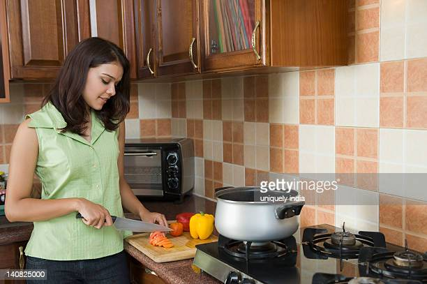 Woman chopping vegetables in a kitchen
