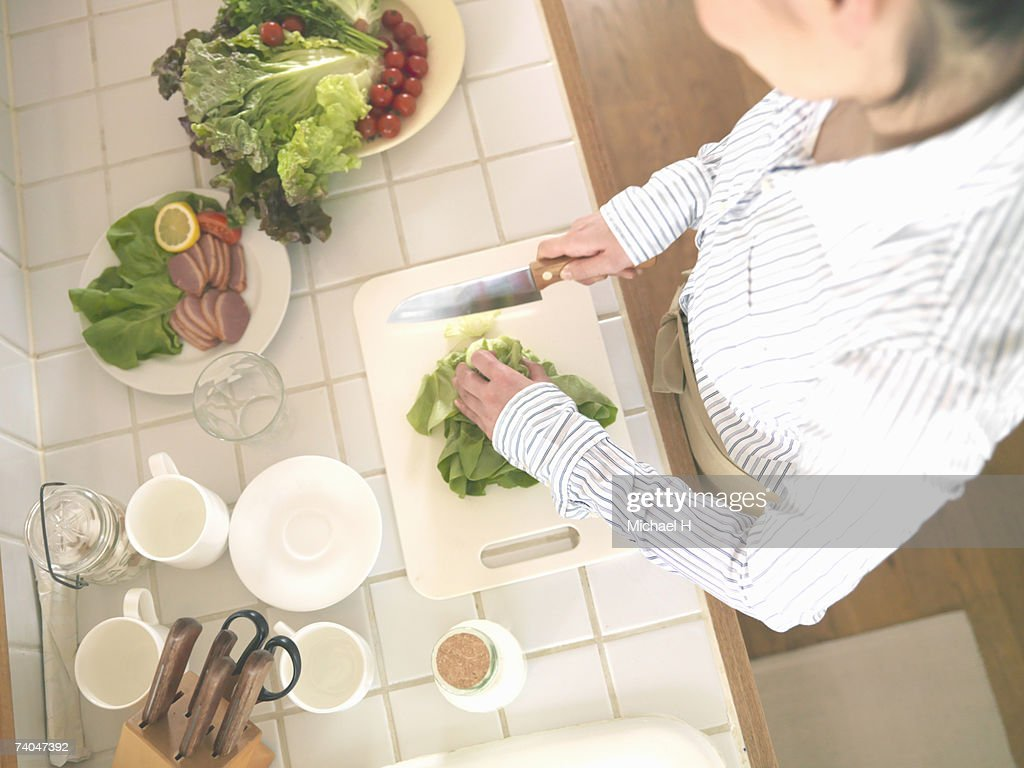 Woman chopping vegetables in kitchen, mid section, elevated view : Stock Photo