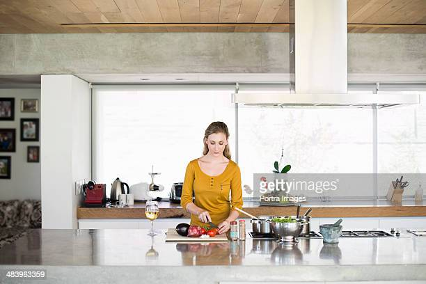 Woman chopping vegetables in kitchen