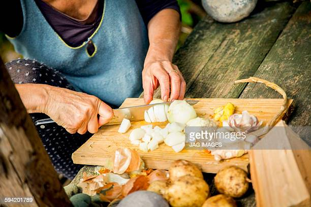 woman chops vegetables on a wooden board