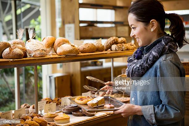 A woman chosing breads in bakeryshop.