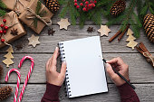 Woman writing Christmas letter or New Year goals on paper on wooden background with decorations, top view, copy space