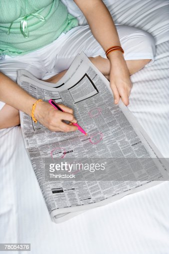 Woman circling want ads in newspaper