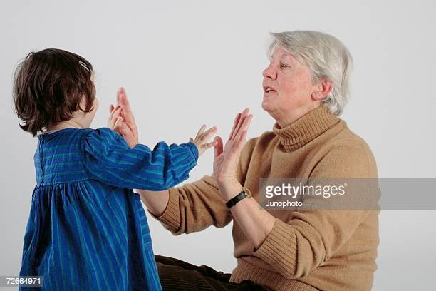 Woman clapping hands with young girl