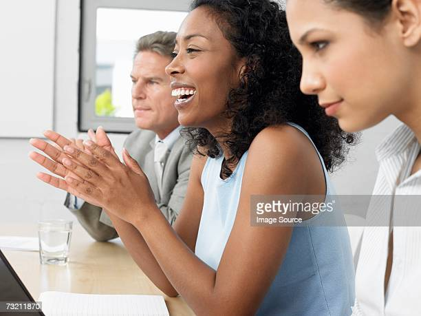 Woman clapping in a meeting