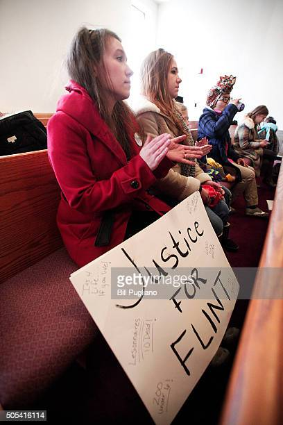 A woman claps during a rally about the Flint water crises at the Heavenly Host Baptist Church January 17 2016 in Flint Michigan US President Barack...