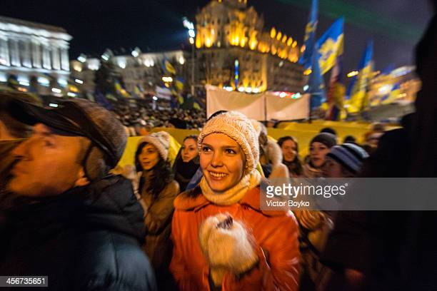 A woman claps in support of Okean Elzy rock band as they perfom on stage in Maidan Square as protests continue on December 14 2013 in Kiev Ukraine...