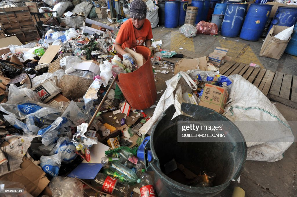 A woman classifies garbage at La Alqueria Recycling Center in Bogota, Colombia, on January 17, 2013. Some 60 recyclers classify 10 tons daily of potentially recyclable waste at this recycling center wich is part of Bogota's Mayor program 'Basura Cero' (Zero waste). AFP PHOTO/Guillermo LEGARIA