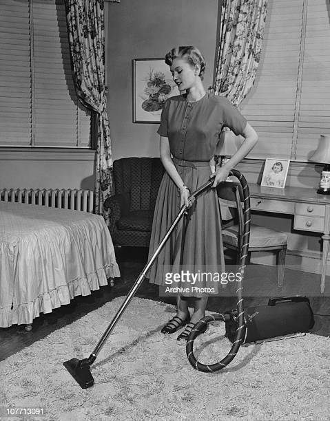 A woman cleaning a bedroom carpet with a vacuum cleaner circa 1940's