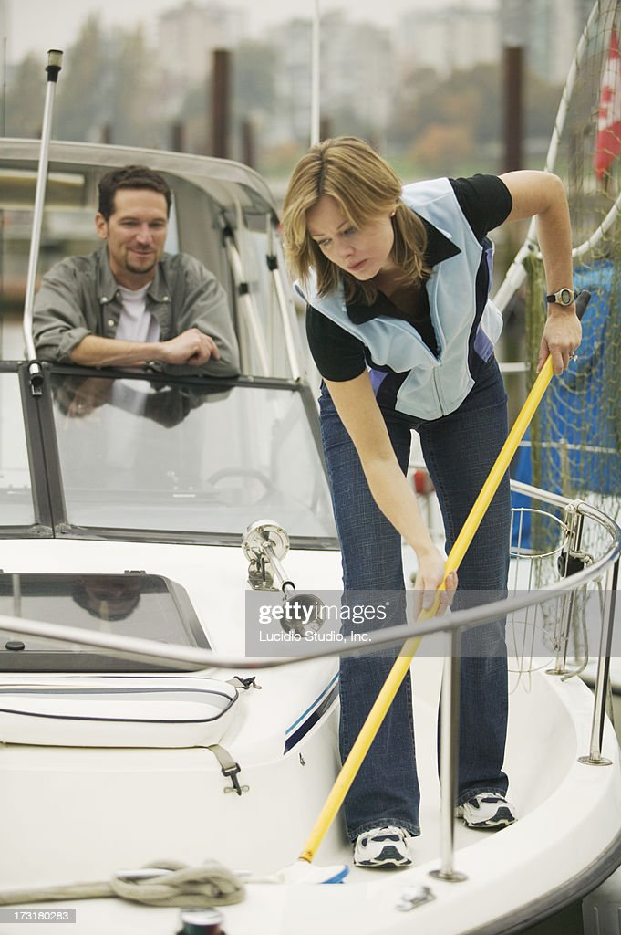 Woman cleaning a boat as her husband looks on : Stock Photo
