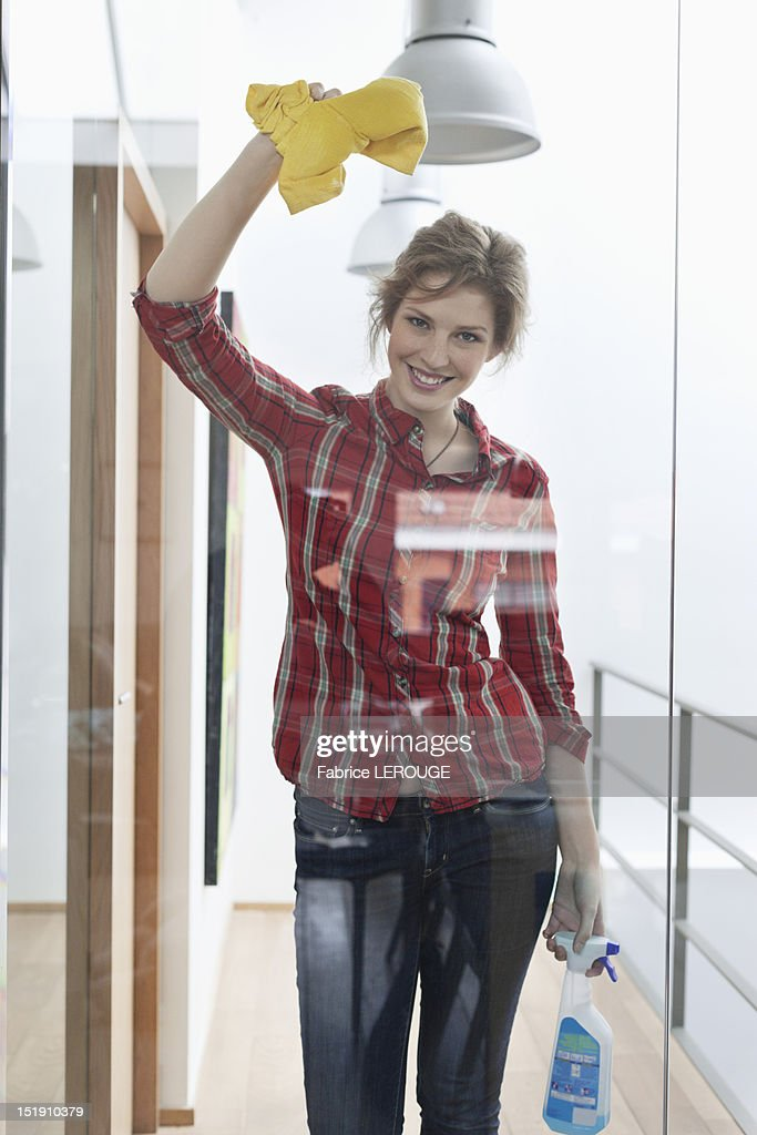 Woman cleaning a glass door and smiling : Stock Photo