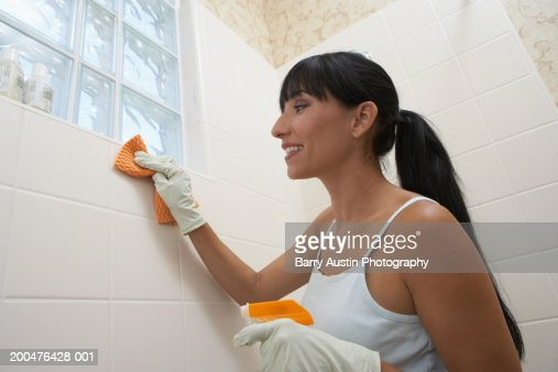Woman cleaning bathroom tiles, smiling, low angle view : Stock Photo