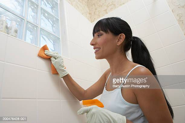 Woman cleaning bathroom tiles, smiling, low angle view