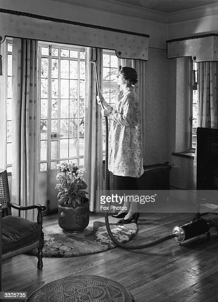 A woman cleaning curtains with a vacuum cleaner