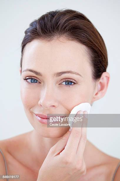 Woman cleaning face with cotton wool