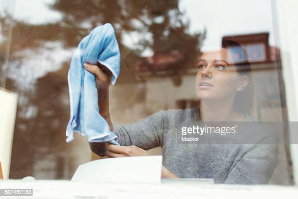 Woman cleaning glass of house window
