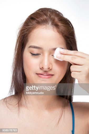 Woman cleaning her face with cotton swab : Stockfoto