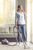 Beautiful young woman in earphones is using a vacuum cleaner, looking out the window and smiling while cleaning her house
