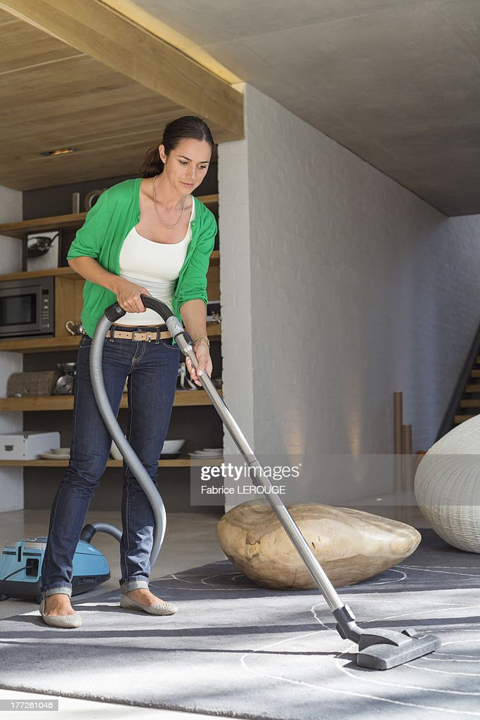 Woman cleaning house with a vacuum cleaner : Stock Photo