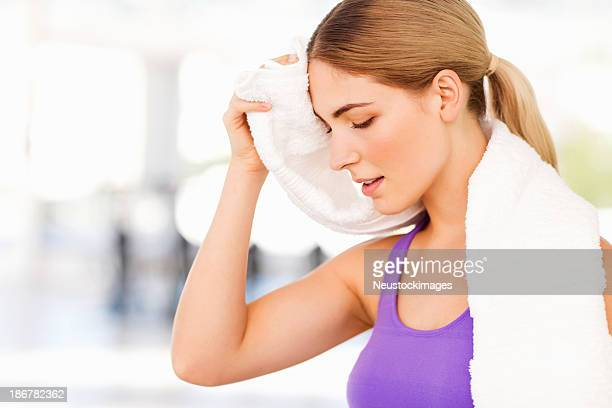 Woman Cleaning Sweat From Forehead After Workout At Gym
